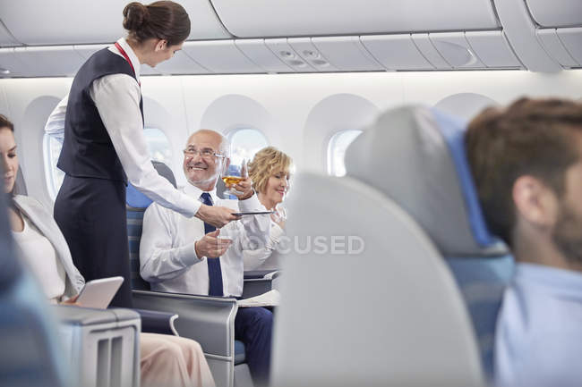 Flight attendant serving whiskey to businessman in first class on airplane - foto de stock