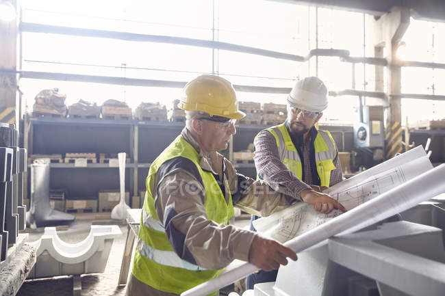 Steelworker and engineer reviewing blueprints in steel mill — Stock Photo