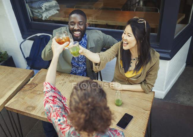 Энтузиазма друзьями поджаривания свежий сок очки на тротуаре кафе — стоковое фото