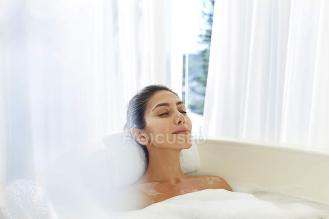 Serene woman enjoying bubble bath with eyes closed — Stock Photo