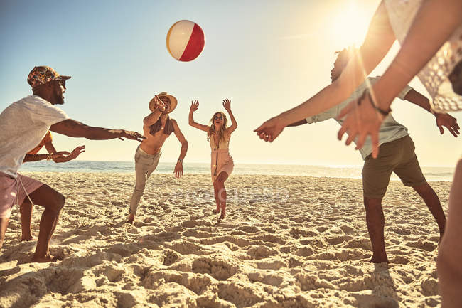 Playful young friends playing with beach ball on sunny summer beach — Stock Photo