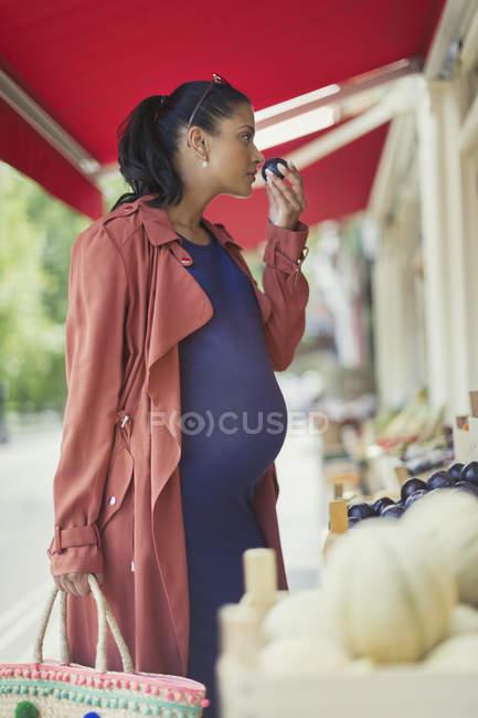 Mujer embarazada de compras, huele a fruta en la tienda del mercado - foto de stock
