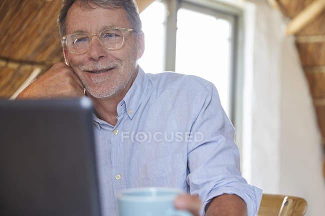 Senior trinkt Kaffee und benutzt Laptop — Stockfoto