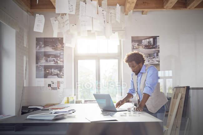Progettista grafico maschio che lavora al computer portatile in ufficio — Foto stock
