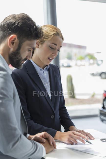 Car saleswoman explaining financial contract paperwork in car dealership — Stock Photo