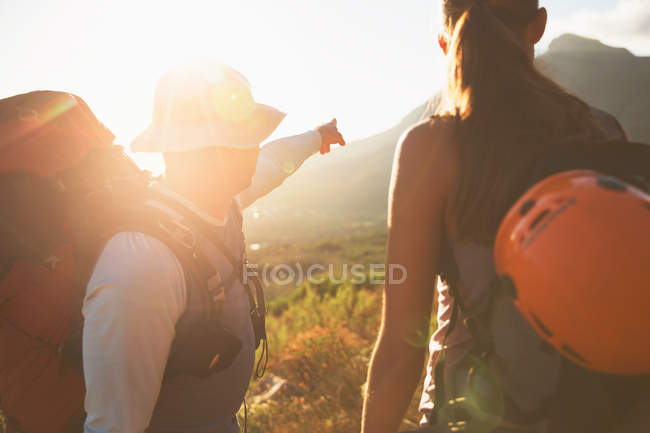 Rock climbers pointing to sunny mountain — Stock Photo