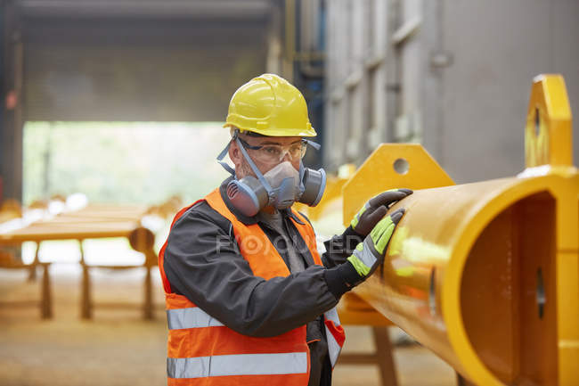 Male worker wearing protective mask in factory — Stock Photo
