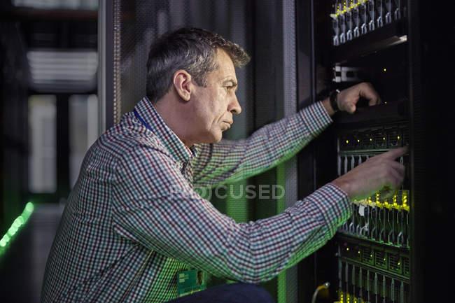 Специализированный IT-техник, работающий на панели в темной серверной — стоковое фото