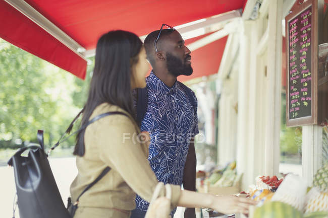 Young couple shopping for produce, looking at prices at outdoor market — Fotografia de Stock