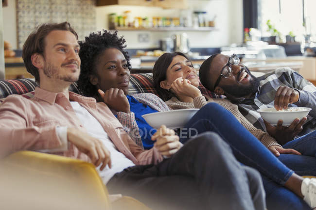 Couples watching TV and eating popcorn on living room sofa — Stock Photo