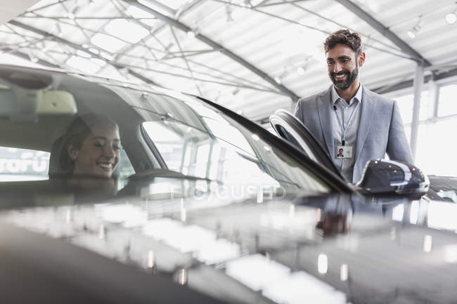 Smiling car salesman and female customer in driver?s seat of new car in car dealership showroom — Stock Photo