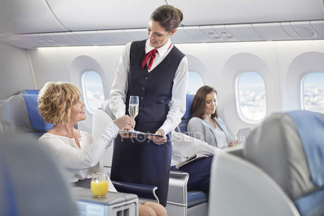 Flight attendant serving champagne to woman in first class on airplane - foto de stock