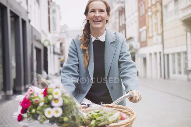 Sonriente bicicleta de equitación de mujer con flores en canasta - foto de stock