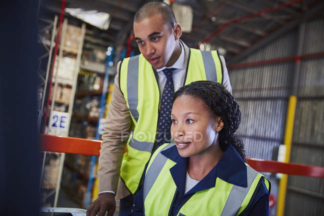 Manager and worker working in distribution warehouse — Stock Photo