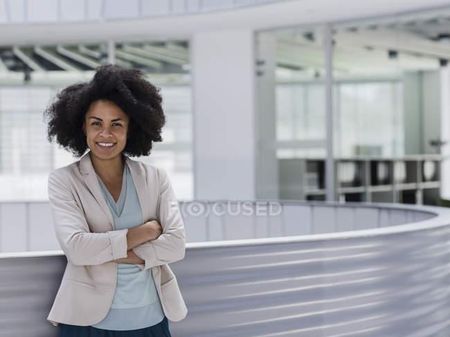 Ritratto donna d'affari sicura e sorridente con le braccia incrociate nell'atrio dell'ufficio — Foto stock