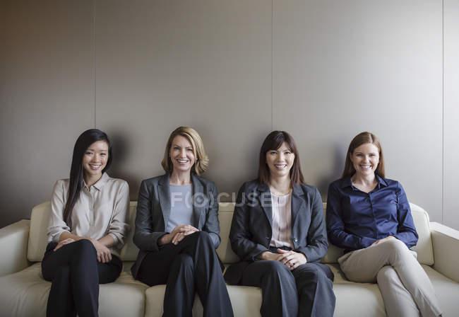 Портрет улыбающихся деловых женщин, сидящих в ряд на диване — стоковое фото
