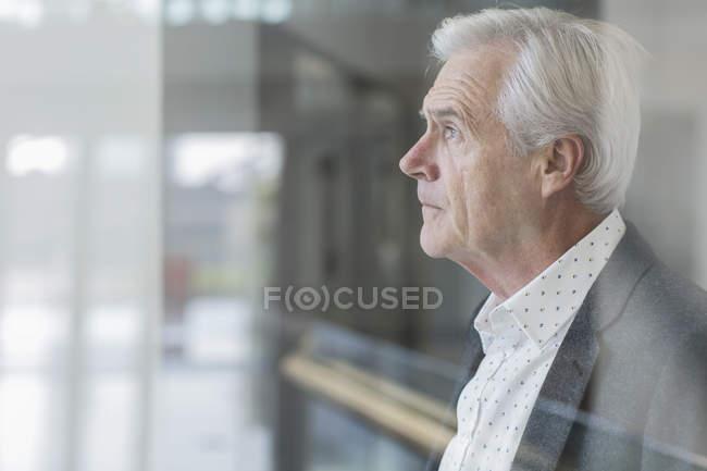 Uomo d'affari pensieroso guardando fuori dalla finestra dell'ufficio — Foto stock
