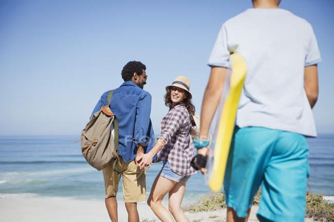 Passeggiata in famiglia con boogie board sulla soleggiata spiaggia estiva sull'oceano — Foto stock