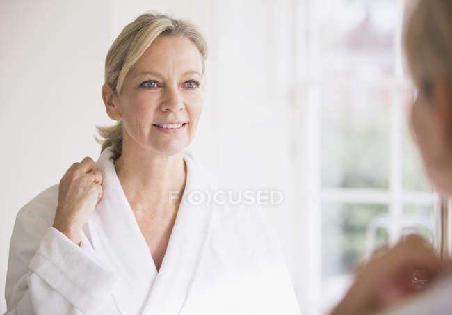 Улыбаясь зрелая женщина в халат в ванной комнате зеркало — стоковое фото