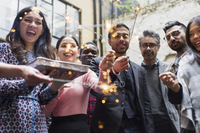 Friends with sparklers and cake celebrating at party — Stock Photo