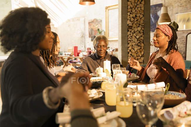 Семья из нескольких поколений держалась за руки, молилась за рождественским ужином — стоковое фото