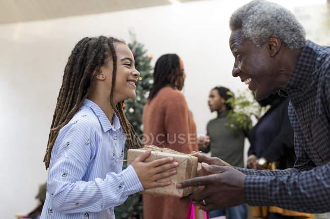 Glücklicher Opa schenkt Enkelin ein Weihnachtsgeschenk — Stockfoto