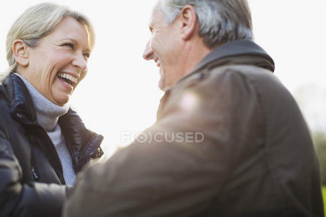 Mature caucasian couple hugging at park and looking at each other — Stock Photo