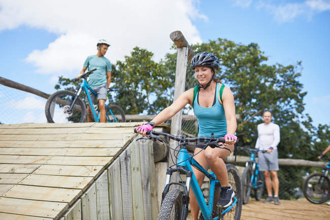 Smiling young woman mountain biking at obstacle course — Stock Photo