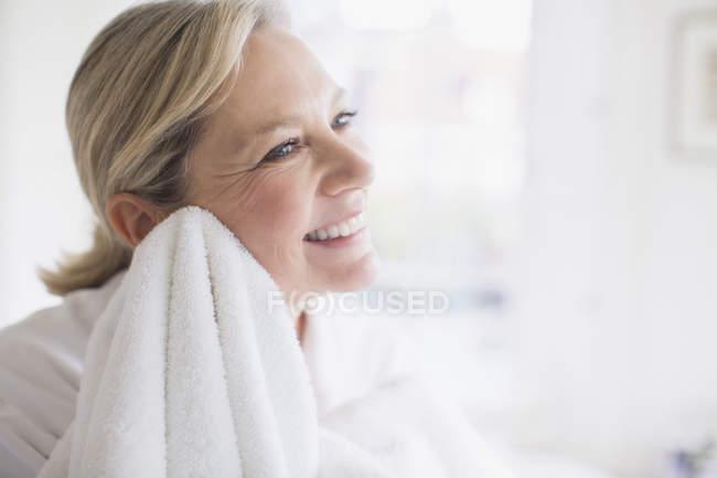 Sonriente mujer madura cara secado con toalla - foto de stock
