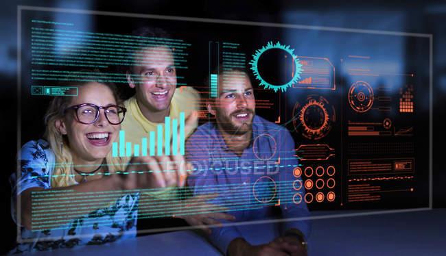 Enthusiastic business people using futuristic hologram computer — Stock Photo