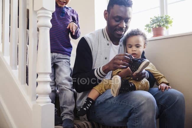 Pai colocando sapatos em bebê filho nas escadas — Fotografia de Stock
