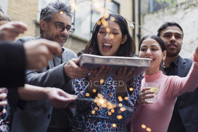 Friends celebrating with man holding birthday cake — Stock Photo