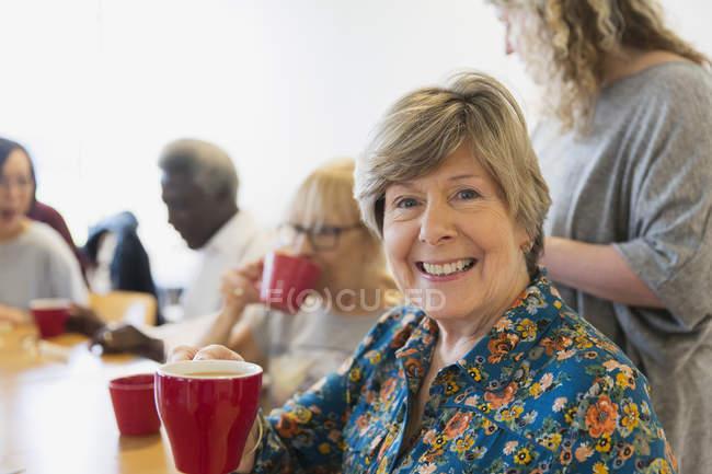 Портрет, посміхаючись, впевнено старший жінка п'є чай з друзями в общинний центр — стокове фото