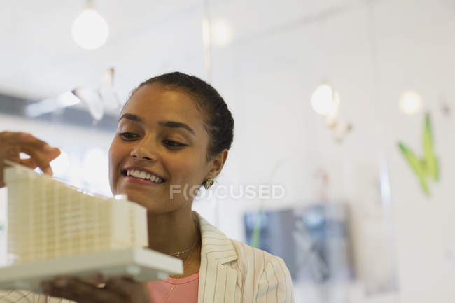 Smiling, confident female architect examining model in office — Stock Photo