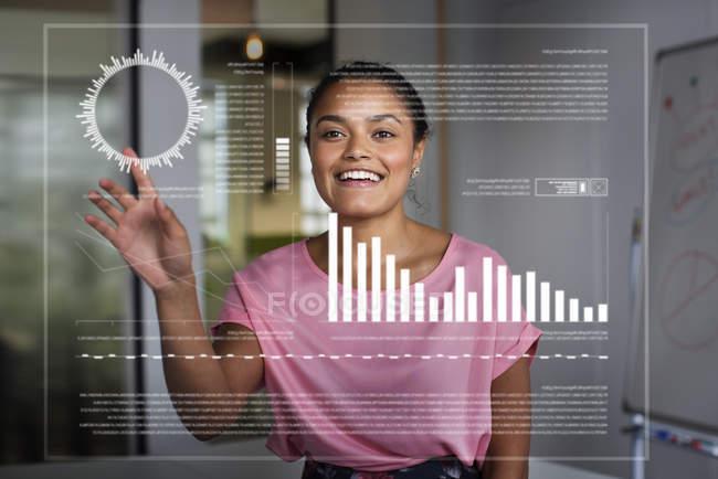 Улыбающаяся, увлеченная деловая женщина, использующая футуристический голографический компьютер — стоковое фото