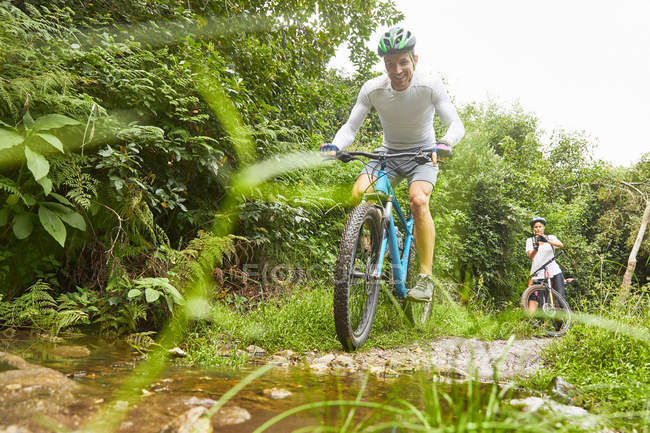 Man mountain biking on muddy trail — Stock Photo