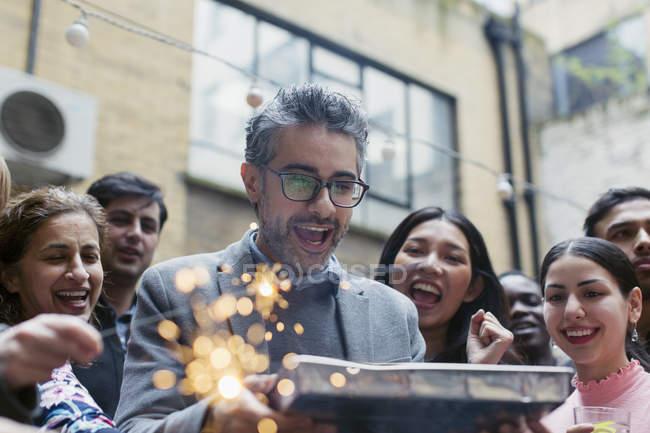 Друзья, празднование с мужчина держит торт ко дню рождения — стоковое фото