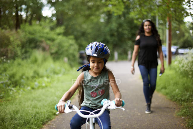Mother watching daughter bike riding on path — Stock Photo
