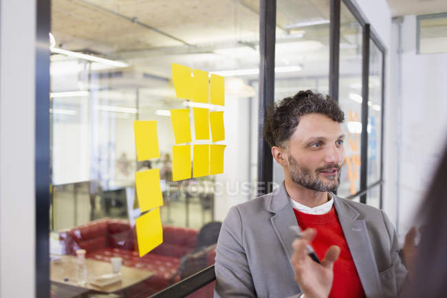 Creative businessman brainstorming with adhesive notes in office — Stock Photo