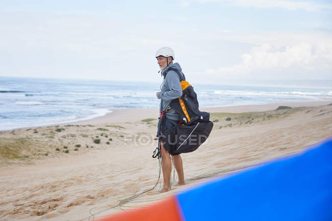 Parapente com mochila de para-quedas na praia do oceano — Fotografia de Stock