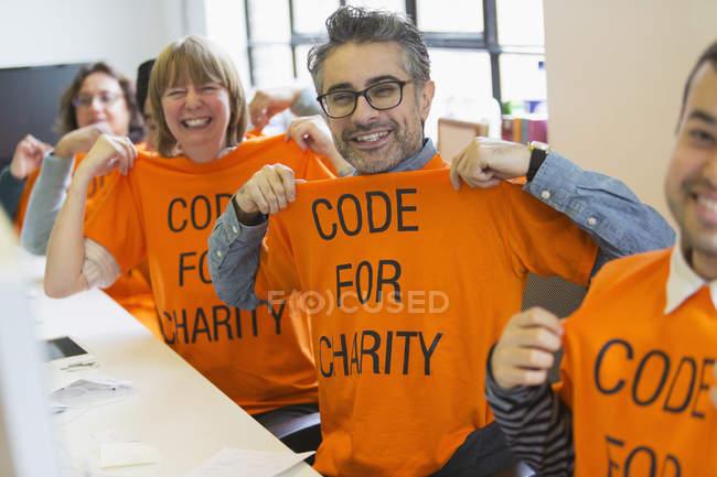 Портрет уверенных хакеров в футболках, кодирующих для благотворительности на хакатоне — стоковое фото