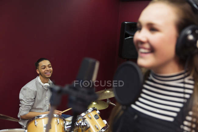 Smiling teenage musicians recording music, signing and playing drums in sound booth — Stock Photo