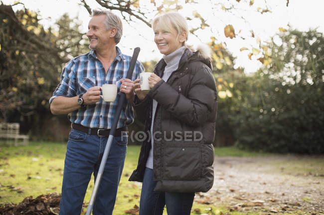 Mature caucasian couple with rakes drinking coffee at garden — Stock Photo