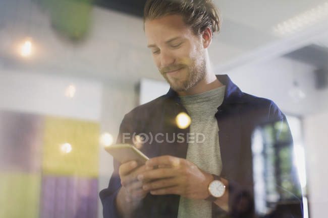 Uomo d'affari sorridente sms con smart phone — Foto stock