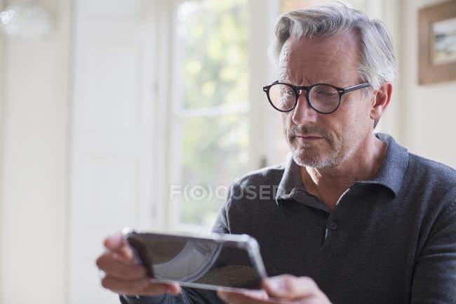 Focada homem maduro usando telefone inteligente em casa moderna — Fotografia de Stock