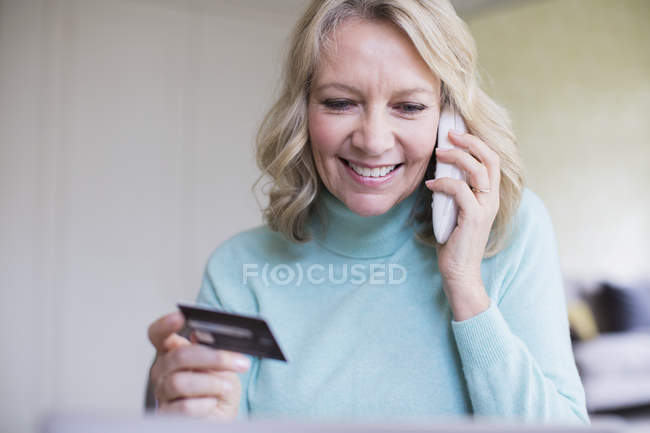 Smiling mature woman with credit card talking on telephone — Stockfoto