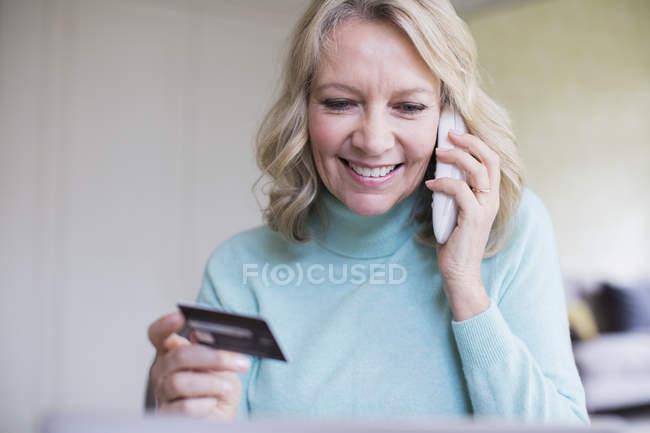 Lächelnd Reife Frau mit Kreditkarte am Telefon sprechen — Stockfoto