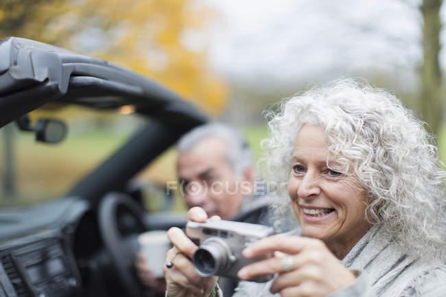 Lächelndes Seniorenpaar mit Digitalkamera im Cabrio — Stockfoto