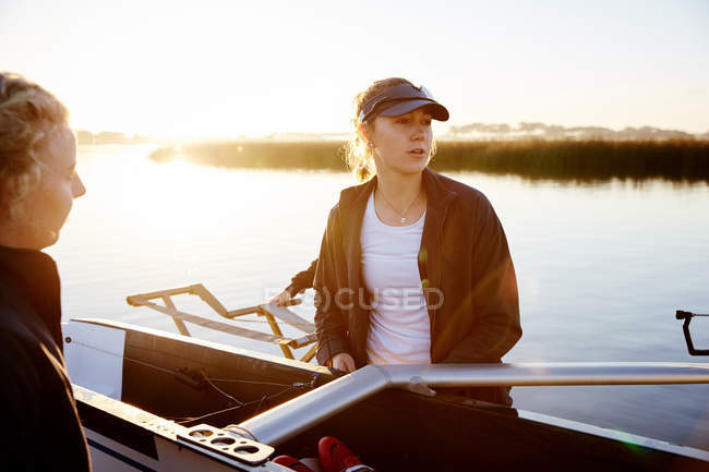 Focused female rower lifting scull at sunrise lakeside — Stock Photo