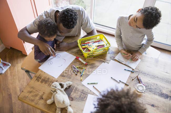 Африканских отец и дети раскраски столом — стоковое фото